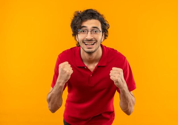 Jovem sorridente, de camisa vermelha e óculos ópticos, segurando os punhos isolados na parede laranja