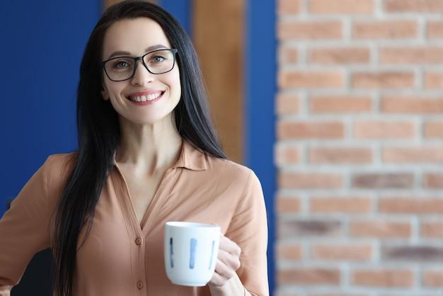 Jovem sorridente de óculos segurando uma caneca com café