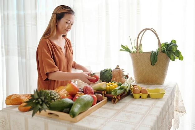 Jovem sorridente desfazendo sacolas de mantimentos que comprou no mercado local e colocando frutas e vegetais em bandejas