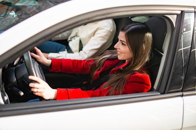 Jovem sorridente dirigindo o carro dela