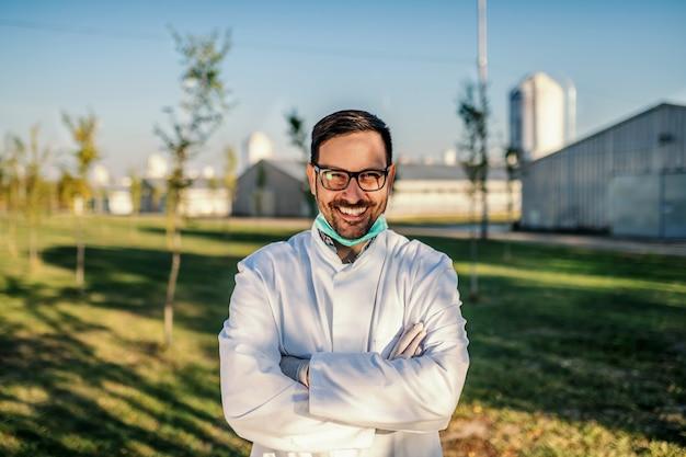 Jovem sorridente e atraente agrônomo caucasiano com uniforme de proteção em pé no pomar