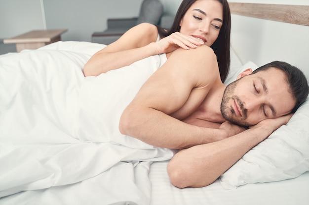 Jovem sorridente e atraente de cabelos escuros deitada na cama, acordada ao lado de seu lindo marido adormecido