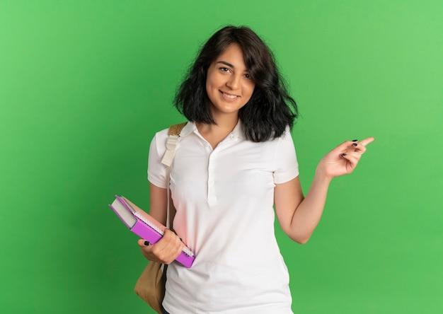 Jovem sorridente e bonita caucasiana colegial com uma bolsa nas costas apontando para o lado segurando livros em verde com espaço de cópia