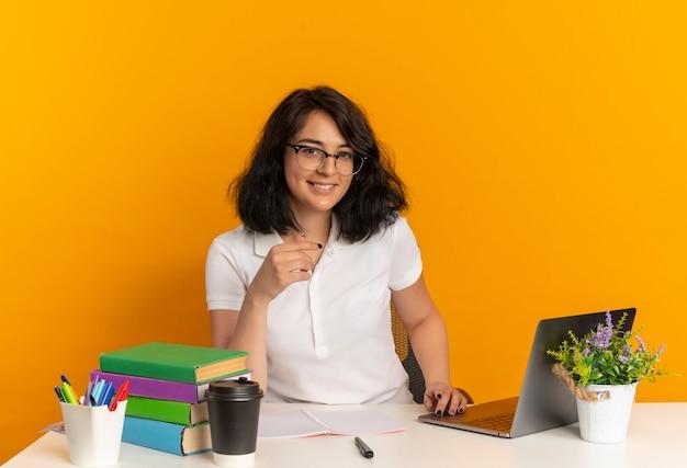 Jovem sorridente e bonita caucasiana colegial de óculos sentada na mesa com as ferramentas escolares isoladas no espaço laranja com espaço de cópia