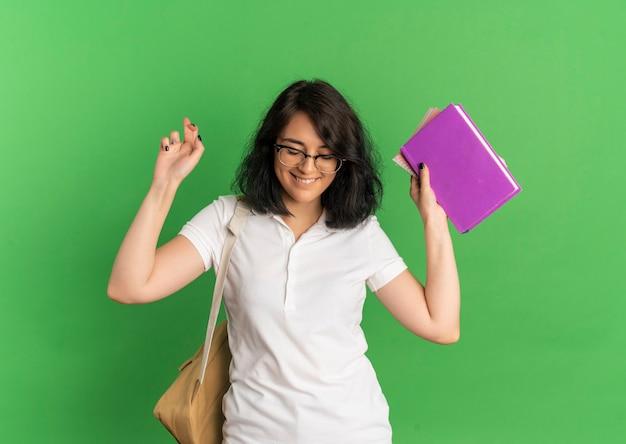 Jovem sorridente e bonita caucasiana colegial usando óculos e bolsa traseira cruza os dedos segurando livros olhando para o verde com espaço de cópia