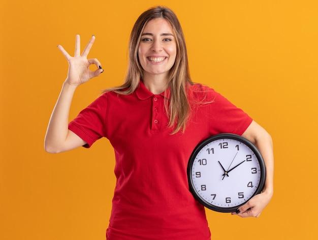 Jovem sorridente e bonita caucasiana gesticulando com a mão ok sinal e segurando o relógio laranja