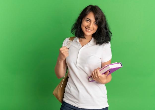 Jovem sorridente e bonita caucasiana, usando uma bolsa traseira, segurando livros, olhando para a câmera em verde com espaço de cópia