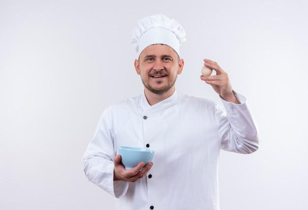 Jovem sorridente e bonito cozinheiro em uniforme de chef segurando uma tigela e um ovo isolado no espaço em branco
