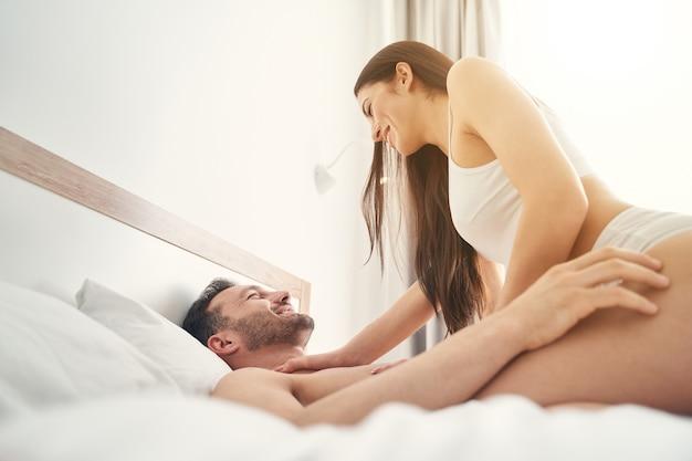Jovem sorridente e brincalhona em lingerie sentada em cima do marido feliz na cama