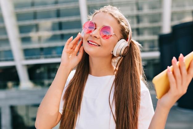 Jovem sorridente e dançando segurando um smartphone e ouvindo música em fones de ouvido