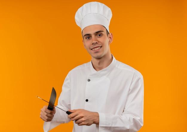 Jovem sorridente e descolado usando uniforme de chef afiar facas