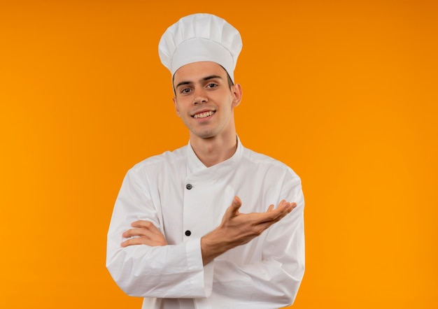 Jovem sorridente e descolado vestindo uniforme de chef aponta lado a lado com espaço de cópia