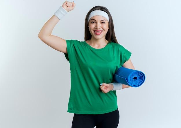 Jovem sorridente e desportiva com fita para a cabeça e pulseiras, segurando o tapete de ioga levantando o punho
