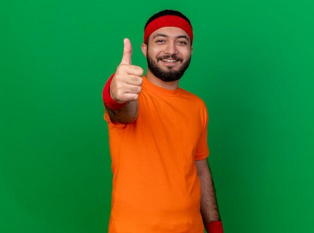 Jovem sorridente e desportivo usando bandana e pulseira aparecendo o polegar isolado no fundo verde