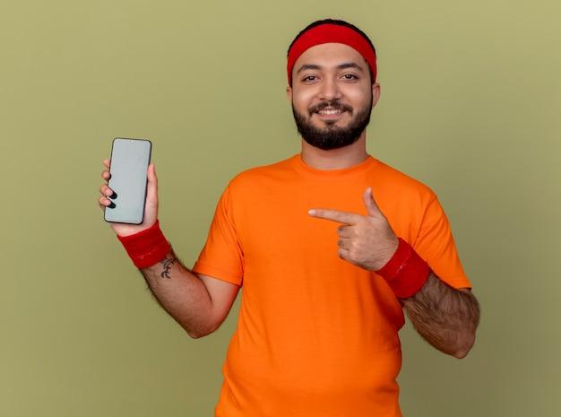 Jovem sorridente e desportivo usando bandana e pulseira segurando e apontando para o telefone isolado em verde oliva