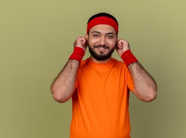 Jovem sorridente e desportivo usando bandana e pulseira segurando orelhas isoladas em verde oliva