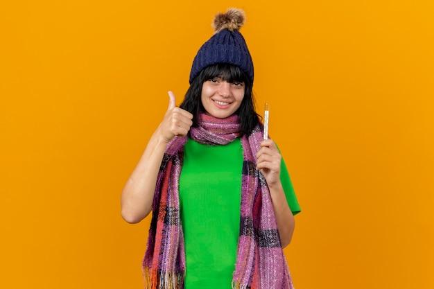 Jovem sorridente e doente caucasiana com chapéu de inverno e lenço segurando o termômetro e mostrando o polegar isolado na parede laranja com espaço de cópia