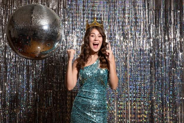 Jovem sorridente e encantadora usando um vestido azul verde brilhante com lantejoulas com coroa e apontando para cima na festa
