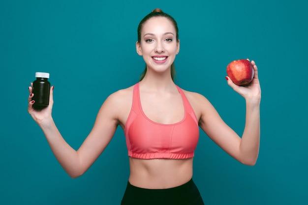 Jovem sorridente e esportiva mostrando maçã e comprimidos ou drogas em um fundo verde isolado