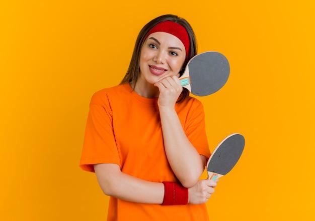 Jovem sorridente e esportiva usando bandana e pulseiras segurando raquetes de pingue-pongue, colocando a mão no queixo e olhando para o lado