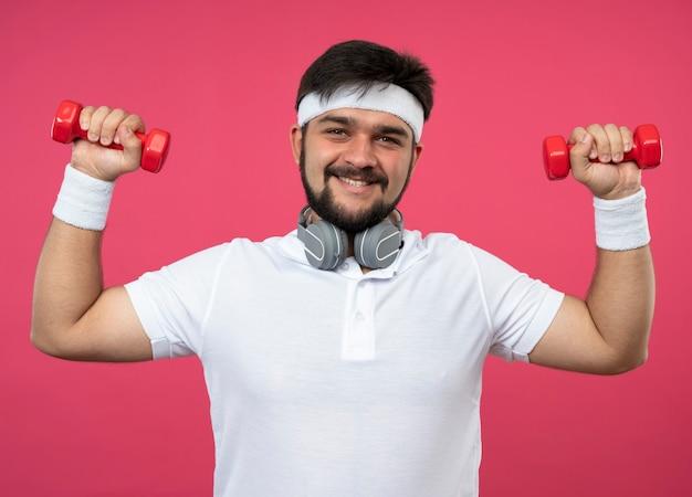 Jovem sorridente e esportivo usando bandana e pulseira com fones de ouvido, fazendo exercícios com halteres