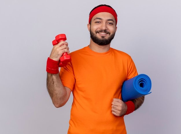 Jovem sorridente e esportivo usando bandana e pulseira segurando halteres