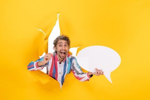 Jovem sorridente e feliz apontando para uma página em branco com espaço livre em um buraco rasgado em papel amarelo
