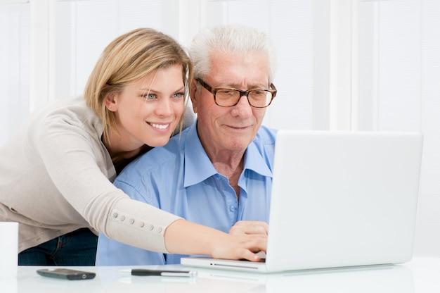 Jovem sorridente e feliz ensinando e mostrando novas tecnologias de computador para o avô