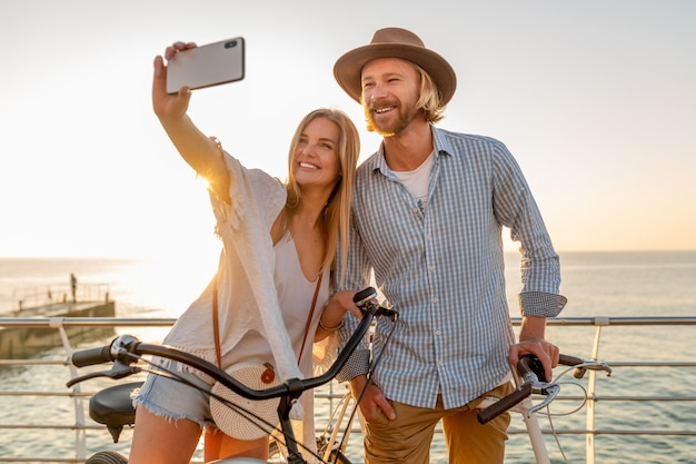 Jovem sorridente e feliz, homem e mulher viajando de bicicleta, tirando uma foto de selfie na câmera do telefone