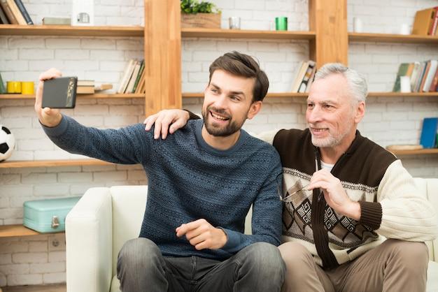 Jovem sorridente e homem envelhecido tomando selfie em smartphone no sofá