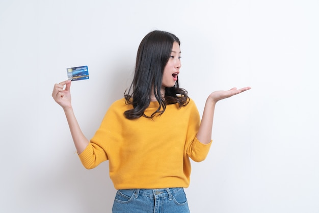 Jovem sorridente e linda mulher asiática apresentando cartão de crédito na mão, mostrando confiança e segurança para fazer o pagamento