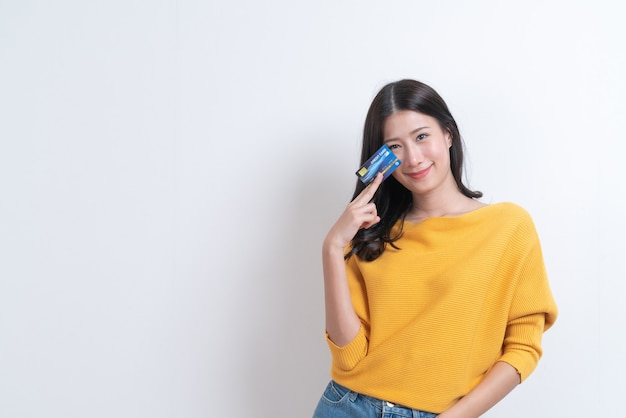 Jovem sorridente e linda mulher asiática apresentando cartão de crédito na mão