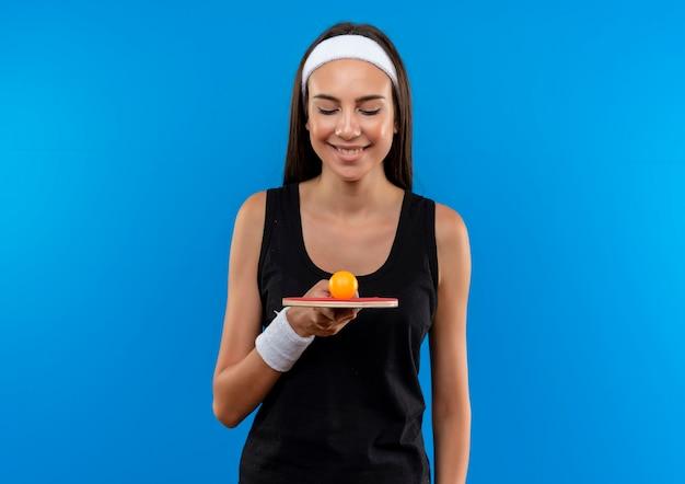 Jovem sorridente e muito esportiva usando bandana e pulseira segurando e olhando para a raquete de pingue-pongue com bola no espaço azul