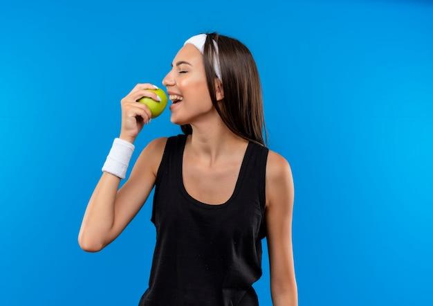 Jovem sorridente e muito esportiva usando bandana e pulseira, segurando e tentando morder uma maçã com os olhos fechados, isolado no espaço azul