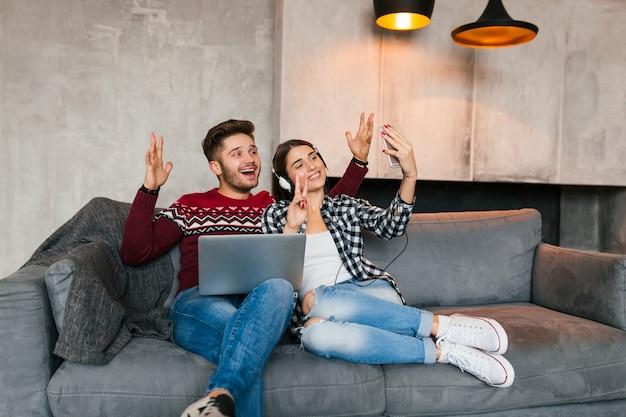 Jovem sorridente e mulher sentada em casa no inverno, segurando laptop, ouvindo fones de ouvido, casal em momentos de lazer juntos, fazendo selfie foto na câmera do smartphone, feliz, positivo, namorando