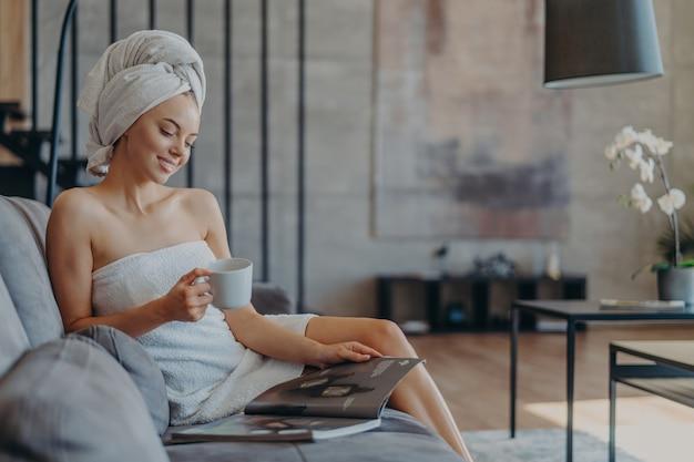 Jovem sorridente e relaxada enrolada em uma toalha depois de tomar banho, bebe café e lê revista de beleza