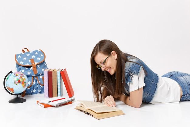 Jovem sorridente e relaxada estudante em roupas jeans e óculos, lendo um livro perto da mochila globo, livros escolares isolados
