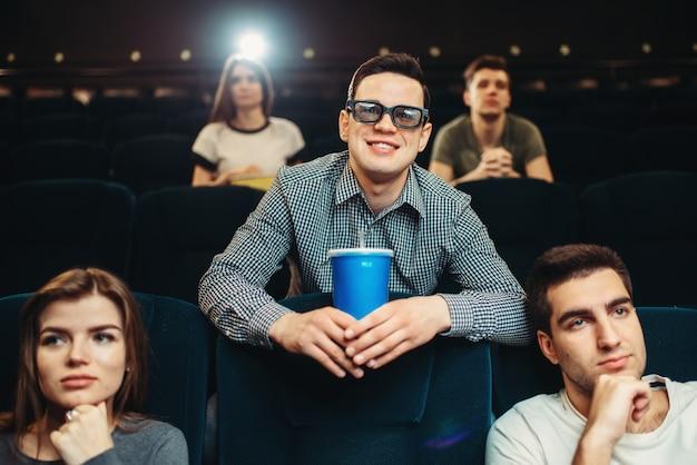 Jovem sorridente em óculos 3d detém bebidas e poses no cinema. showtime, indústria do entretenimento, assistir filmes