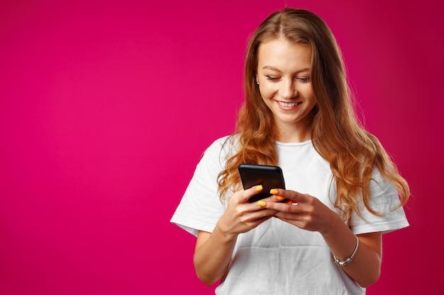 Jovem sorridente em pé e usando seu smartphone contra rosa