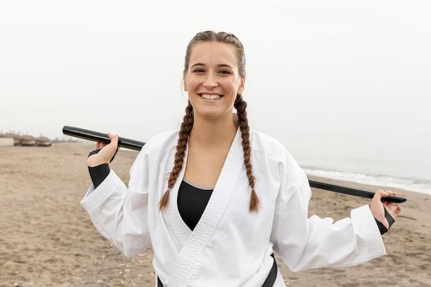 Jovem sorridente em traje de arte marcial