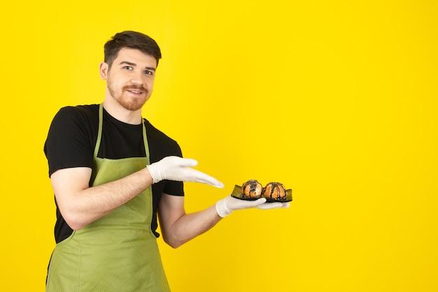 Jovem sorridente em um amarelo apresentando muffins caseiros.