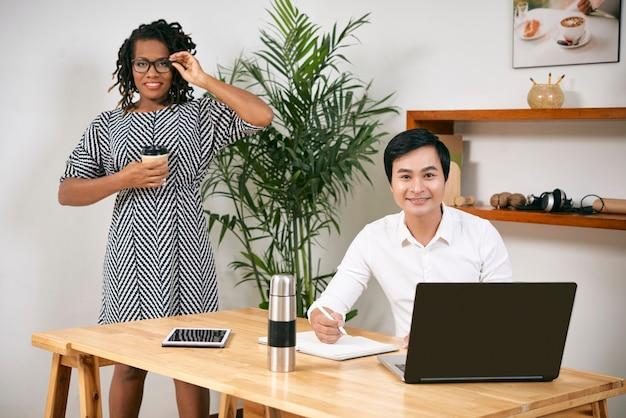 Jovem sorridente empresária asiática trabalhando em um laptop e preenchendo o planejador quando seu colega está tomando café da manhã