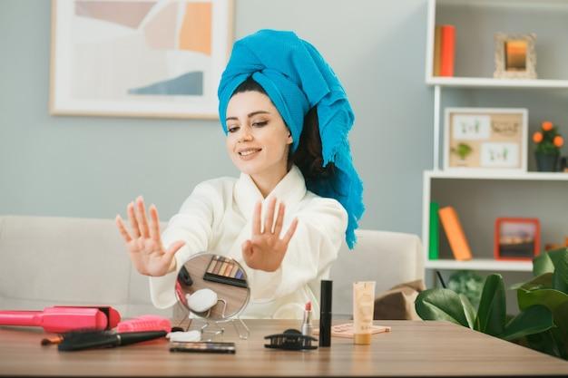 Jovem sorridente enrolada em uma toalha de cabelo com unhas de gel secas, sentada à mesa com ferramentas de maquiagem na sala de estar