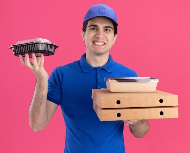 Jovem sorridente entregador de uniforme azul e boné segurando pacotes de pizza com um pacote de comida de papel neles e um recipiente de comida na outra mão, olhando para a frente, isolado na parede rosa