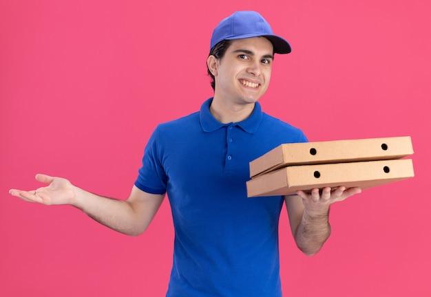 Jovem sorridente entregador de uniforme azul e boné segurando pacotes de pizza, olhando para a frente, mostrando a mão vazia isolada na parede rosa