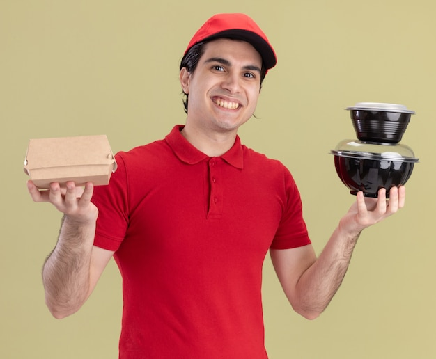 Jovem sorridente entregador de uniforme vermelho e boné segurando um pacote de comida de papel e recipientes de comida olhando para a frente, isolado na parede verde oliva