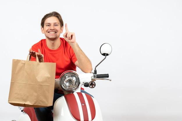 Jovem sorridente entregador de uniforme vermelho sentado na scooter segurando um saco de papel e aparecendo na parede branca
