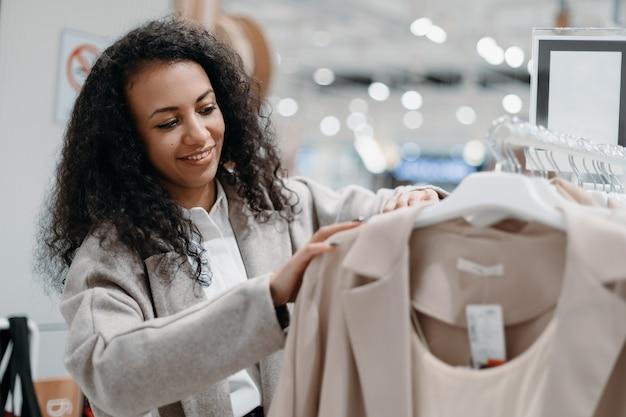 Jovem sorridente escolhendo um casaco na loja