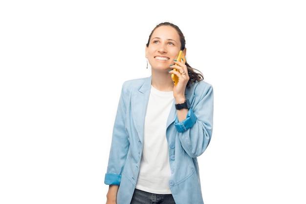 Jovem sorridente está falando ao telefone em pé sobre um fundo branco.