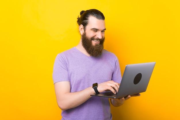 Jovem sorridente está segurando seu laptop, digitando algo nele.